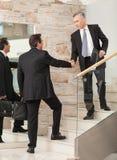 Geschäftsmänner, die Hände auf Schritten rütteln Lizenzfreie Stockbilder
