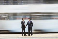 Geschäftsmänner, die Hände auf verkehrsreicher Straße rütteln Stockbild