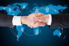 Geschäftsmänner, die Hände gegen Weltkarte rütteln Lizenzfreies Stockfoto