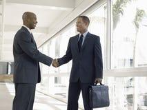Geschäftsmänner, die Hände im Büro-Korridor rütteln Lizenzfreie Stockbilder
