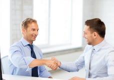 Geschäftsmänner, die Hände im Büro rütteln Lizenzfreies Stockbild