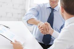 Geschäftsmänner, die Hände im Büro rütteln Stockbild