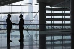 Geschäftsmänner, die Hände im Flughafenabfertigungsgebäude rütteln Stockfoto