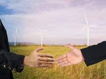 Geschäftsmänner, die Hände mit Windkraftanlagebauernhof rütteln Weltweites ener Stockfotos