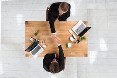 Geschäftsmänner, die Hände am Schreibtisch im Büro rütteln Lizenzfreie Stockfotos