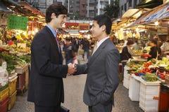 Geschäftsmänner, die Hände am Straßenmarkt- rütteln Lizenzfreie Stockfotos
