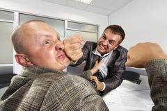 Geschäftsmänner, die im Büro kämpfen Lizenzfreie Stockfotos
