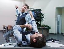 Geschäftsmänner, die im Büro kämpfen Stockfoto