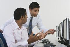 Geschäftsmänner, die im Computer-Labor sich besprechen Lizenzfreie Stockfotografie