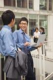 Geschäftsmänner, die mit Laptop lächeln und draußen zusammenarbeiten Stockbild