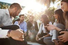 Geschäftsmänner, die mit Mitarbeitern draußen sich besprechen stockfoto