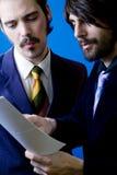 Geschäftsmänner, die Papiere betrachten stockfoto