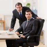 Geschäftsmänner, die Schreibtisch im Büro ernst betrachten Lizenzfreie Stockfotos
