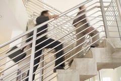 Geschäftsmänner, die sich oben in Büro bewegen Lizenzfreies Stockbild