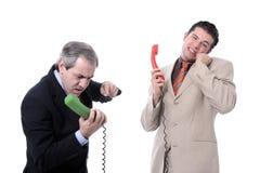Geschäftsmänner, die am Telefon argumentieren Stockbild