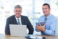 Geschäftsmänner, die zusammen mit Laptop und Tablette arbeiten Lizenzfreie Stockbilder