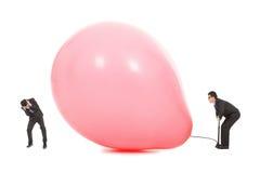 Geschäftsmänner erschrockener Ballon wird aufgeblasen, um zu bersten Stockfotografie