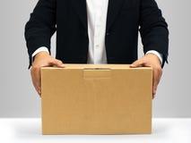 Geschäftsmänner halten auf dem braunen Papierkasten nieder Lizenzfreies Stockfoto
