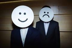 Geschäftsmänner im Lächeln und in den traurigen Masken Lizenzfreies Stockfoto