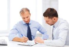 Geschäftsmänner mit Notizbuch auf Sitzung Lizenzfreies Stockbild