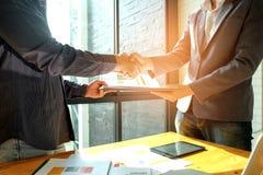 Geschäftsmänner rütteln Hände beim Teilnehmen an der Geschäftsvereinbarung, in Stockfoto