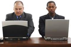 Geschäftsmänner am Schreibtisch mit Laptopen Stockfotos