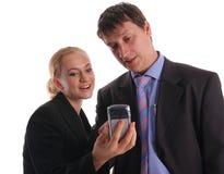 Geschäftsmänner und Geschäftsfraublick in einem Telefon lizenzfreies stockbild