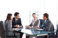 Geschäftsmänner und Geschäftsfrauen, die an einem Tisch sprechen Lizenzfreie Stockfotografie