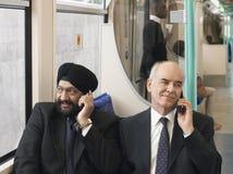 Geschäftsmänner unter Verwendung der Mobiltelefone im Zug Stockbilder