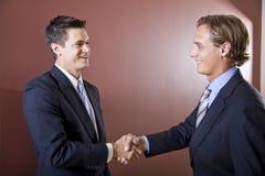 Geschäftsmänner, welche die Anzüge rütteln Hände tragen Lizenzfreie Stockfotos