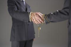Geschäftsmänner, welche die Hände eingewickelt in der Goldkette und -vorhängeschloß rütteln lizenzfreie stockfotos