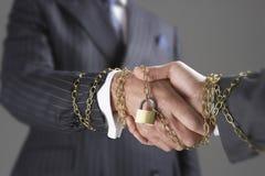 Geschäftsmänner, welche die Hände eingewickelt in der Goldkette und -vorhängeschloß rütteln lizenzfreie stockbilder