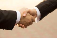 Geschäftsmänner, welche die Hände schließen einen Vertrag rütteln Stockbilder