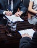 Geschäftsmänner, welche die Vereinbarung unterzeichnen Stockfotografie