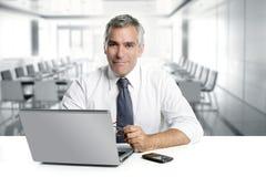 Geschäftsmannälterer, der modernes Innenbüro bearbeitet