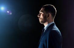 Geschäftsmann über schwarzem Hintergrund mit Blendenfleck Stockbilder
