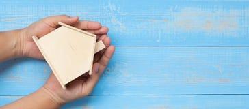 Geschäftsmann übergibt das Halten des Holzhausmodells auf blauer Pastellfarbholztabelle lizenzfreies stockbild