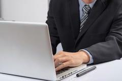 Geschäftsmann übergibt das Schreiben auf einem PC oder einem Laptop Lizenzfreie Stockfotos