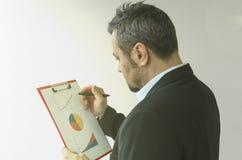 Geschäftsmann überprüft Grafiken auf einem Blatt Papier Stockfotografie