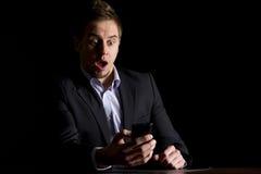 Geschäftsmann überrascht über Textmeldungen stockfoto
