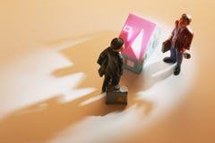 Geschäftsmann-Abbildungen und Spielzeug-Haus Lizenzfreies Stockbild