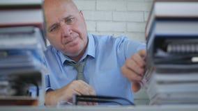 Geschäftsmann In Accounting Archive, das in den Dokumenten und in den Rechnungen sucht stockbilder