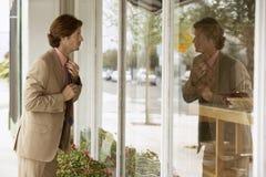 Geschäftsmann Adjusting Tie While, das Glaswand betrachtet Lizenzfreie Stockbilder