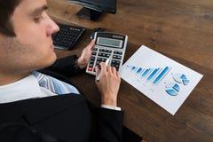 Geschäftsmann Analyzing Financial Data mit Taschenrechner Lizenzfreie Stockfotos