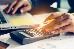 Geschäftsmann arbeiten mit einem Taschenrechner und einem Laptop Im Büro Stockfotos