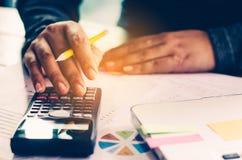 Geschäftsmann arbeiten mit einem Taschenrechner und einem Laptop Im Büro Lizenzfreies Stockfoto