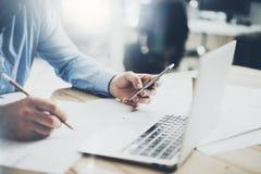Geschäftsmann an Arbeitsplatz Simsender Mitteilungssmartphone und -c$halten von Bleistifthänden Generische Designnotizbuch-Holzta Lizenzfreies Stockbild