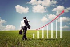 Geschäftsmann auf dem Gebiet mit grünem Gras und blauem Himmel steigt an lizenzfreies stockfoto