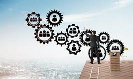 Geschäftsmann auf dem Hausdach, das Teamwork- und Verbindungskonzept darstellt Gemischte Medien Lizenzfreie Stockfotografie