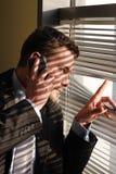 Geschäftsmann auf dem Telefonschauen Stockbild